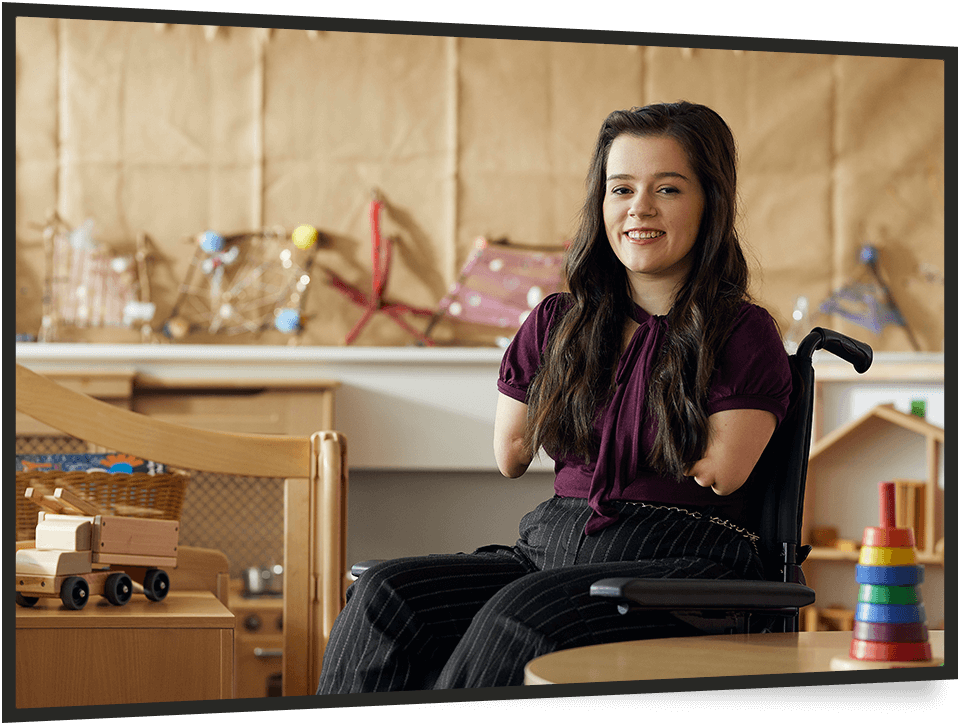 Young woman in a wheelchair working in school nursery