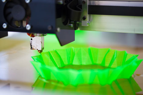Image of a 3D printer, printing a green plastic bowl