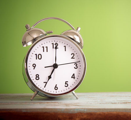 A small silver alarm clock
