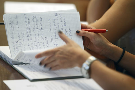 A student taking notes in a lecture. We see hands and a notebook full of writing.