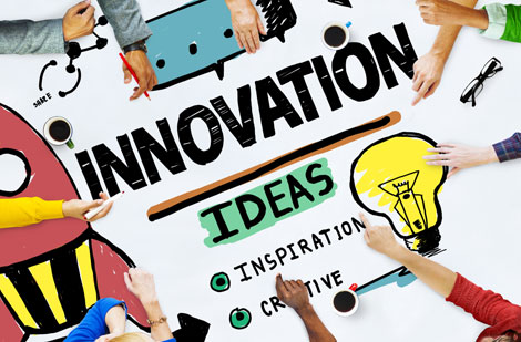 A table with 'Innovation', 'Ideas', 'Inspiration' and 'Creative' written on it, people sit around the table and are moving things in with their hands.