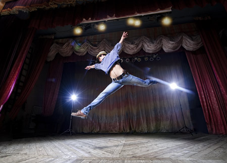 A dancer leaping across the stage