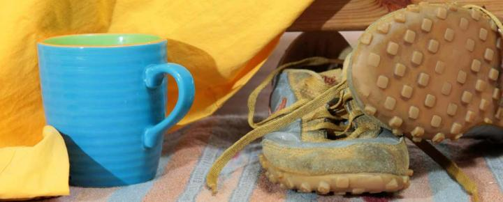 Shoes and a mug of coffee under a bed