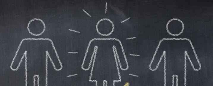 Figures drawn on a chalkboard, one has been selected with a big tick showing the successful interview candidate