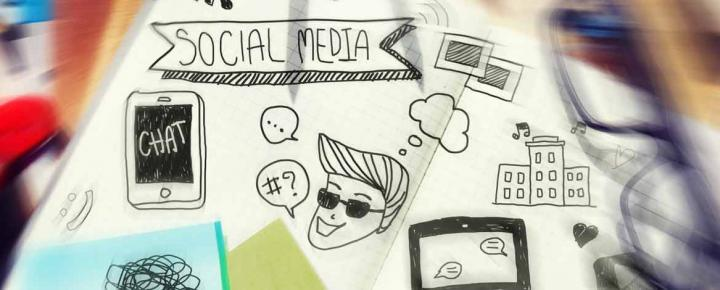 Scribbles of 'social media' and doodles on a page, on a messy desk
