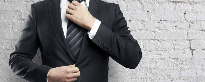 A man straightening his tie, wearing a smart suit