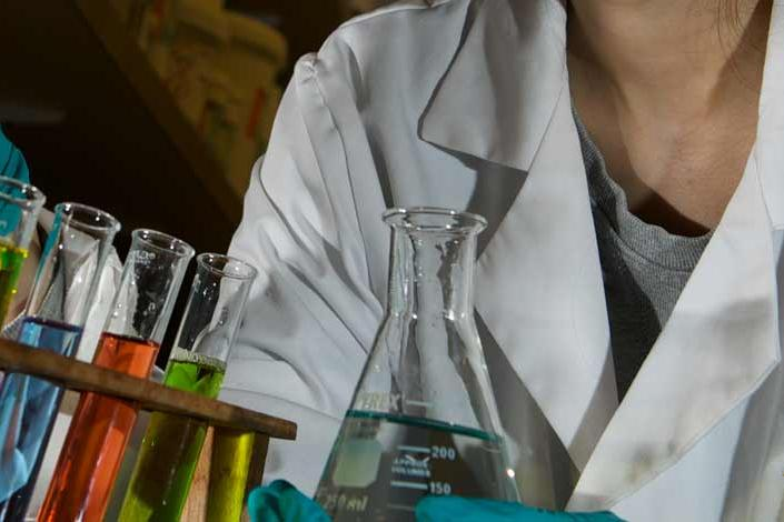A lab technician dropping chemicals into test tubes